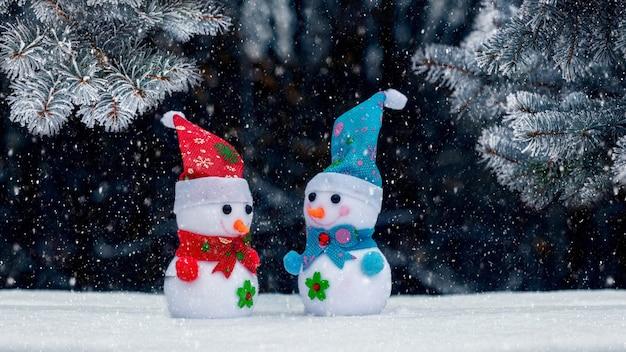 Cartão de natal com bonecos de neve na floresta perto das árvores de natal em um fundo escuro durante a nevasca