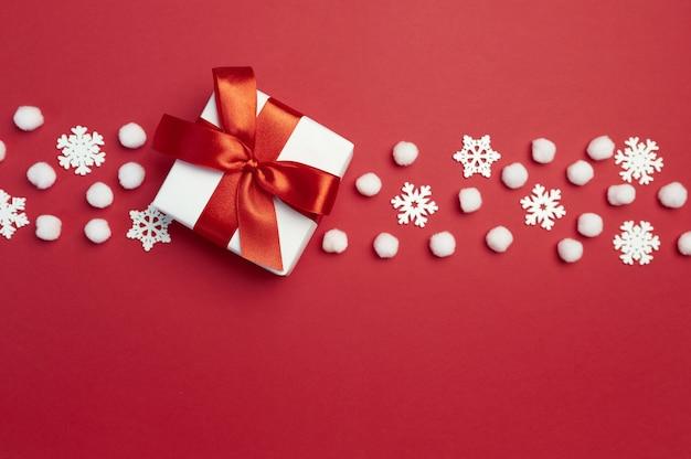 Cartão de natal com caixa de presente com fita vermelha e flocos de neve