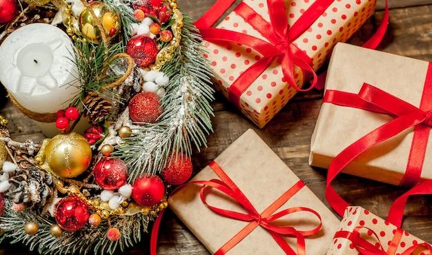 Cartão de natal com caixa de presente e brinquedos em um fundo de madeira.