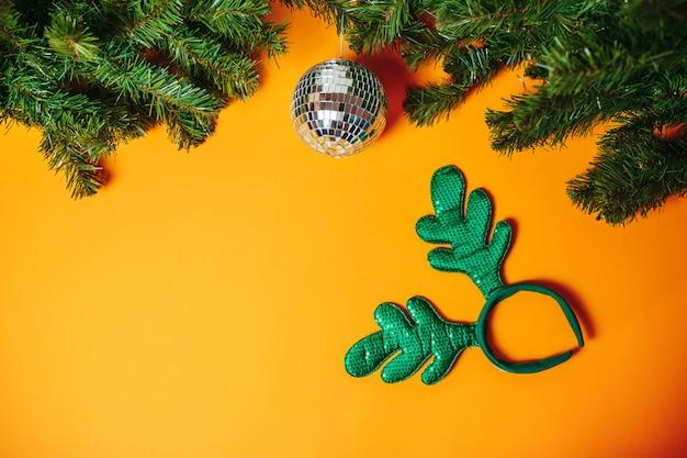 Cartão de natal com copyspace. bola de discoteca de prata e chifres de natal com ramos de abeto ao redor na laranja.