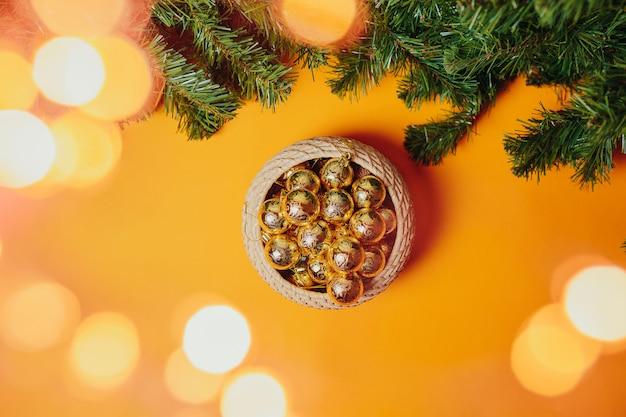 Cartão de natal com copyspace. enfeites de natal plana leigos na laranja. bolas douradas e vermelhas na cesta e abeto ramos ao redor.