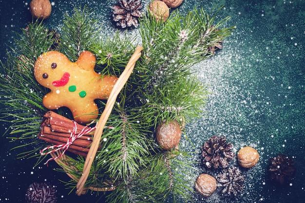 Cartão de natal com homem-biscoito e galhos de coníferas na cesta.