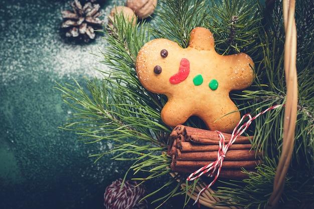 Cartão de natal com homem-biscoito e galhos de coníferas na cesta