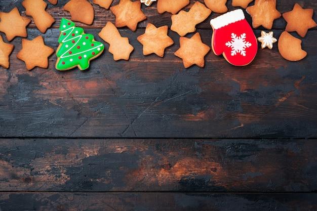 Cartão de natal com pão de mel na velha superfície de madeira. vista do topo