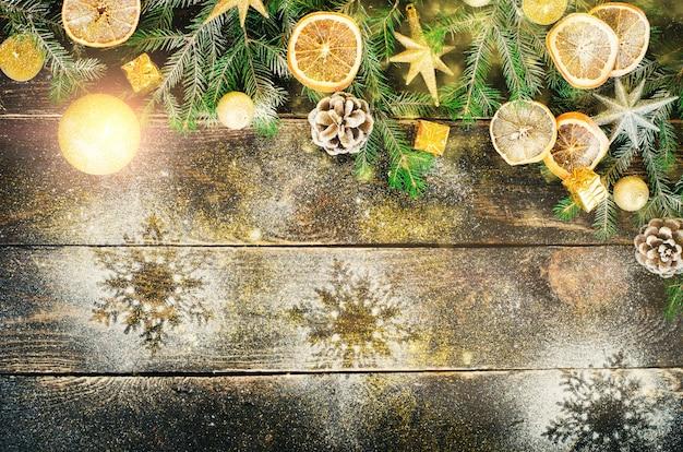 Cartão de natal com presentes, vela, cones, paus de canela, laranja seca, árvore verde