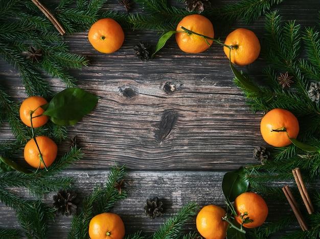 Cartão de natal com tangerinas, ramos de abeto e pinhas