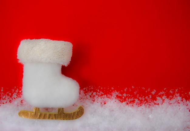Cartão de natal com um patim branco na neve.