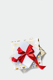 Cartão de natal, convite de aniversário ou dia dos namorados. um grupo de caixas de presente brancas e douradas amarradas com um laço de fita vermelha em uma mesa de luz. vista superior, configuração plana. fundo vertical com espaço