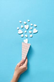 Cartão de natal criativo com cone de papel de pequenos corações de gesso como sorvete de sobremesa na mão de uma mulher
