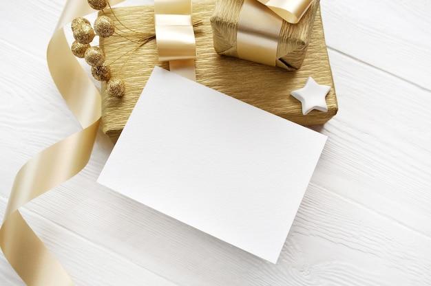 Cartão de natal de maquete com fita dourada para presente, flatlay em um fundo branco de madeira, com lugar para o seu texto