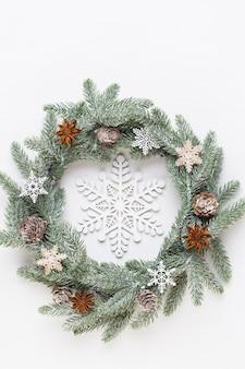 Cartão de natal. decoração de grinalda em fundo branco de madeira. conceito de ano novo. copie o espaço. postura plana. vista do topo.