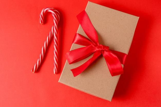 Cartão de natal e ano novo em vermelho com caixa de presente e pirulito.