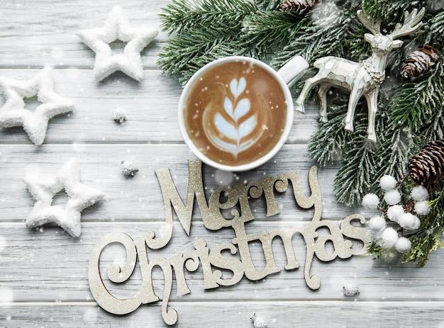 Cartão de natal e feliz ano novo com uma xícara de café, pinho, abeto em fundo branco de madeira, vista superior