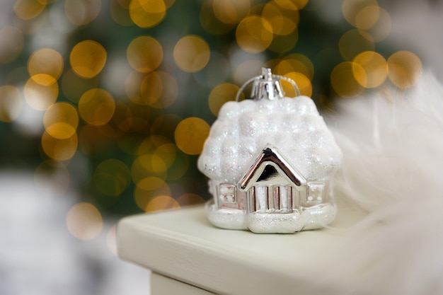 Cartão de natal e plano de fundo. casa de brinquedo branco de vidro de natal na neve, contra um fundo de bokeh amarelo de luzes de guirlanda