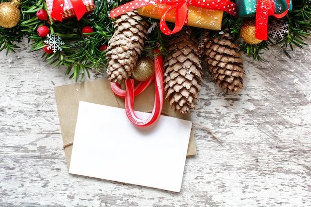 Cartão de natal em branco com galhos de árvores de abeto, decorações, pinhas e caixas de presente