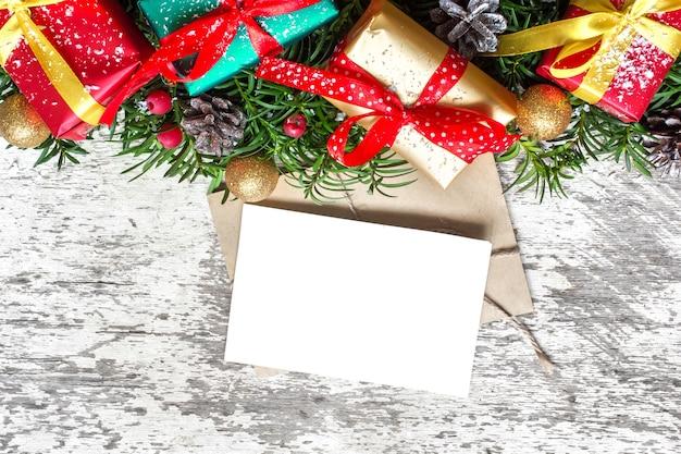 Cartão de natal em branco com galhos de pinheiros, decorações e caixas de presente