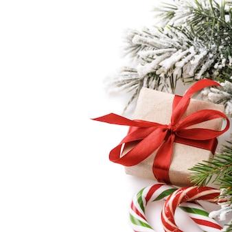 Cartão de natal em um fundo branco com ramo de abeto de doces de presente e espaço de cópia