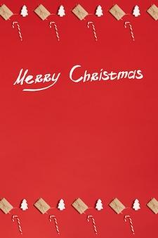 Cartão de natal. fundo vermelho. símbolo do ano novo. cone de doces de natal. carta. copie o espaço