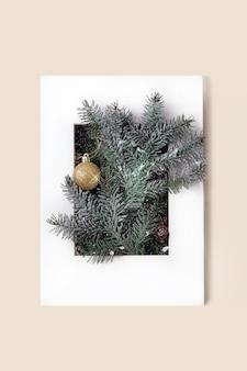 Cartão de natal ou ano novo com galhos de árvore do abeto com bola de natal dourada em moldura de papel branco. fundo bege. postura plana, copie o espaço