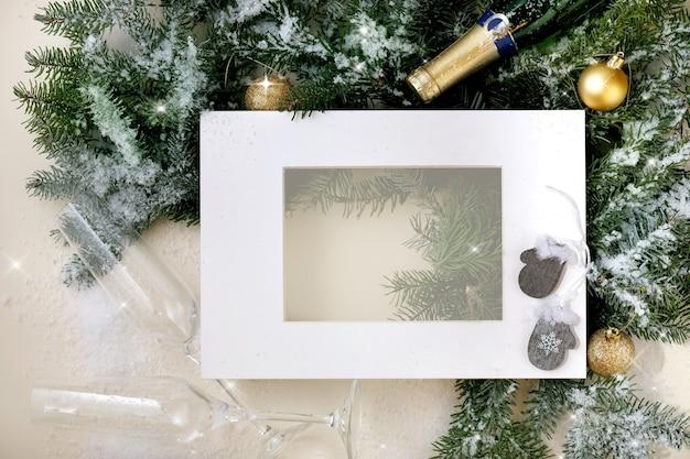 Cartão de natal ou ano novo com galhos de árvore do abeto com bola dourada de natal, copos e garrafa de champanhe, quadro de papel branco. luz dourada do bokeh. fundo bege. postura plana, copie o espaço
