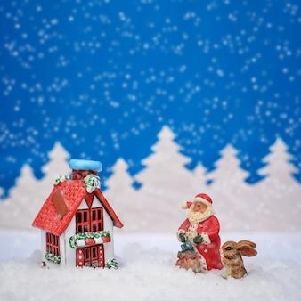 Cartão de natal quadrado com casa vermelha, papai noel e coelho e está nevando