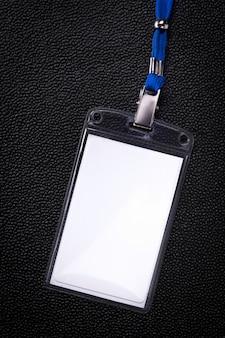 Cartão de negócio de suspensão no fundo escuro. cartão de identificação em branco do crachá.