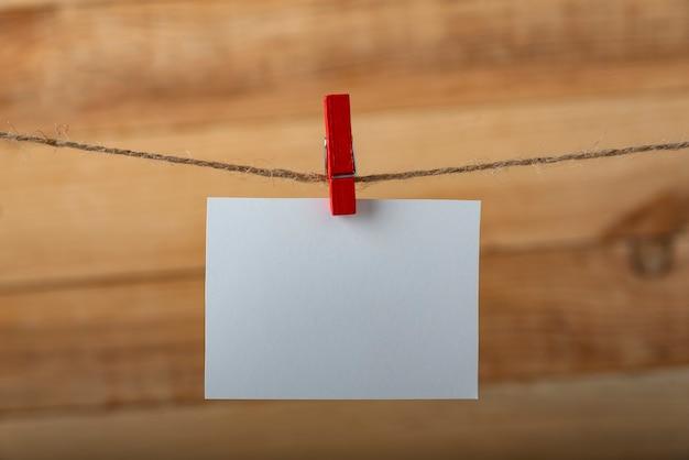 Cartão de nota branco em branco com prendedor de roupa no prendedor de corda da corda. quadro vertical.