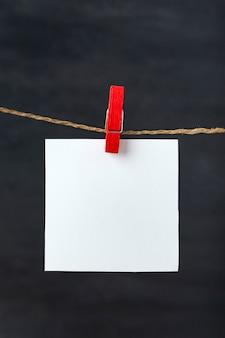 Cartão de nota em branco branco pendurar com prendedor na corda. fundo preto. copie o espaço, maquete.