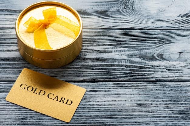 Cartão de ouro cintilante e caixa de presente dourada