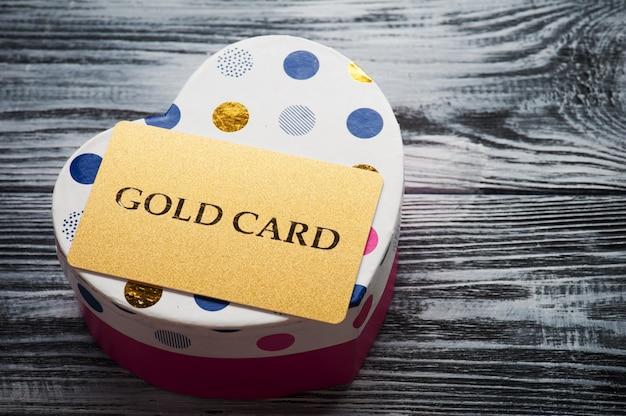 Cartão de ouro cintilante na caixa rosa de forma de coração