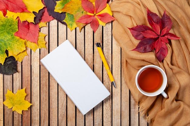 Cartão de outono para seu projeto, vista superior com copyspace. chá quente, caderno branco, caneta amarela, manta laranja, deixa de madeira com espaço em branco para texto. postura plana. relaxamento sazonal