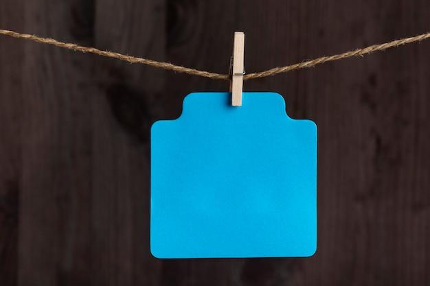 Cartão de papel azul em branco com prendedor de roupa na corda. copie o espaço. lugar para o seu texto. fundo de madeira.