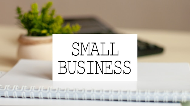 Cartão de papel branco com texto pequenas empresas na calculadora. conceito de negócios.