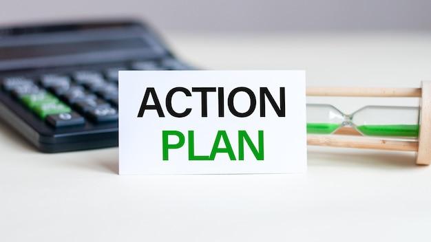 Cartão de papel branco com texto plano de ação folha de papel branco para anotações, calculadora, ampulheta na parede branca. conceito de negócios.