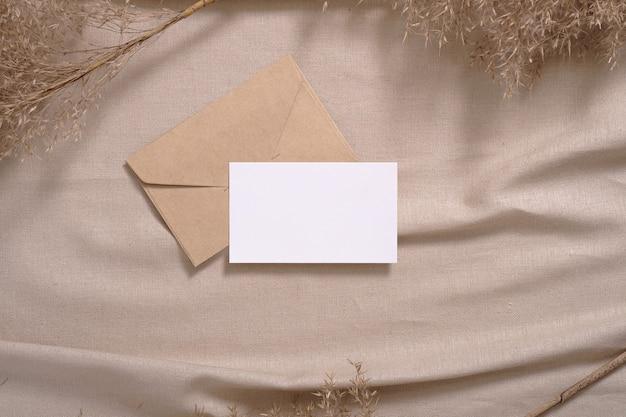 Cartão de papel branco em branco e maquete de envelope com grama seca de pampa em tecido bege