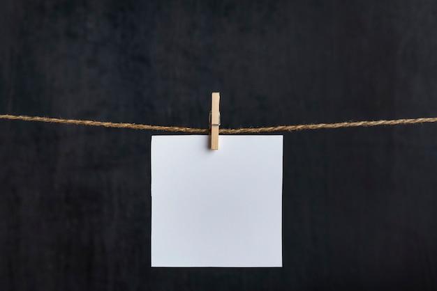 Cartão de papel branco em branco pendurar com prendedores de roupa na corda em fundo preto. copie o espaço. lugar para o seu texto.