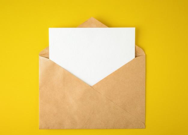 Cartão de papel branco em um envelope em fundo amarelo