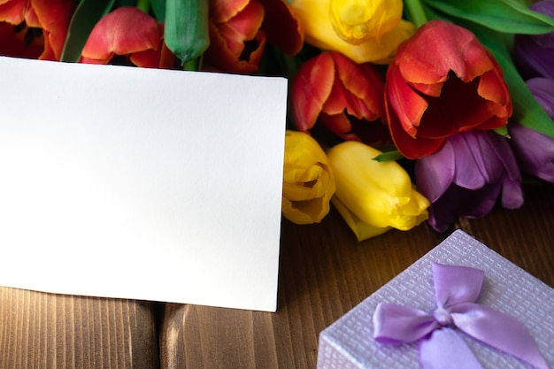 Cartão de papel branco simulado com uma caixa de presente e tulipas em uma mesa de madeira