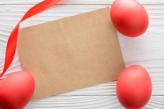 Cartão de papel com brilhantes ovos de páscoa em cima da mesa de madeira.