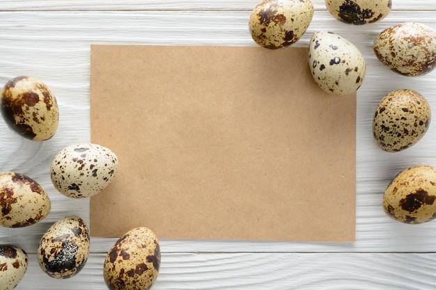 Cartão de papel com ovos de codorna em cima da mesa de madeira.