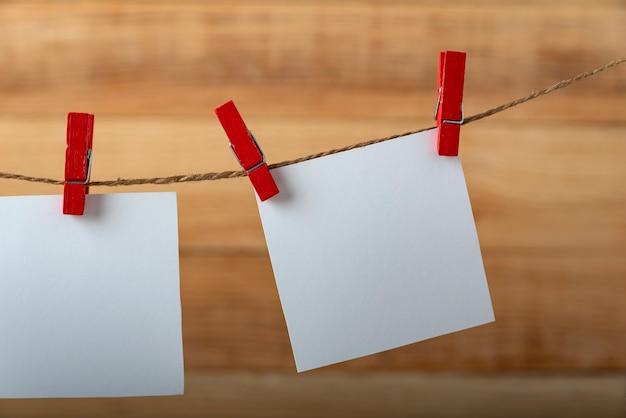 Cartão de papel de nota quadrada em branco pendurado com clipe de madeira ou prendedor de roupa no cabide de corda da corda. copie o espaço.