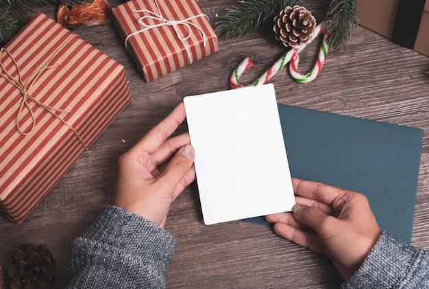 Cartão de papel do tag do modelo com a decoração do natal no fundo de madeira da tabela.