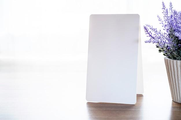 Cartão de papel dobrado em branco ereto na tabela de madeira com espaço branco do fundo e da cópia.