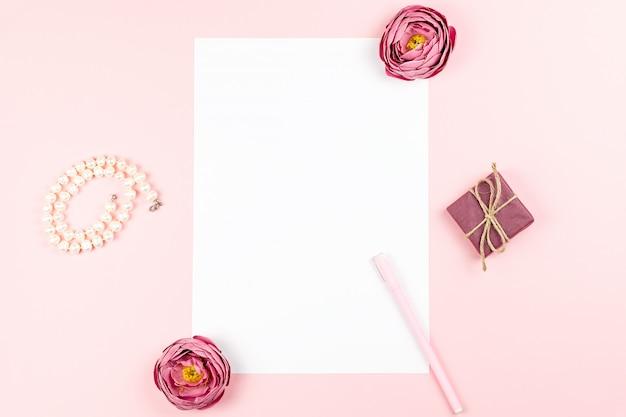 Cartão de papel em branco com caneta, jóias, quadro de flores sobre fundo pastel. vista superior, copie o espaço.