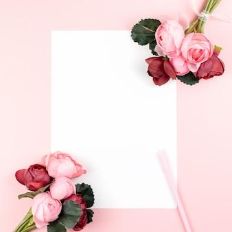 Cartão de papel em branco com caneta, quadro de flores vermelhas e rosa sobre fundo pastel, copie o espaço.