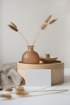 Cartão de papel em branco com grama rabo de coelho, bandeja de madeira, manta bege neutra.