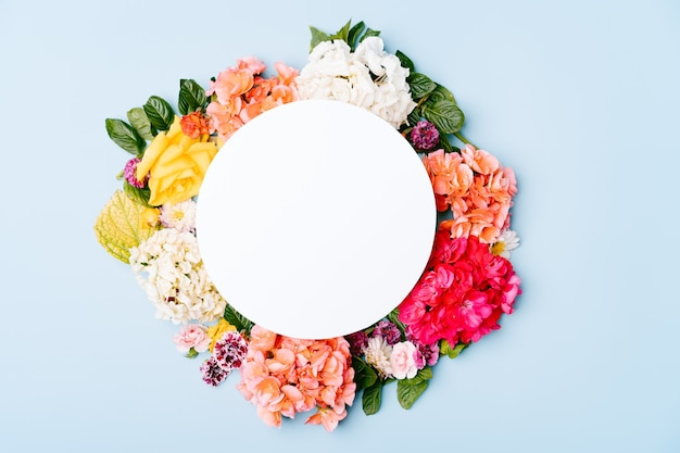 Cartão de papel em branco com moldura floral redonda de flores misturadas em um espaço de cópia de fundo azul pastel