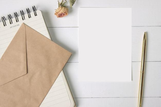 Cartão de papel em branco, envelope, caderno espiral, caneta dourada e uma rosa