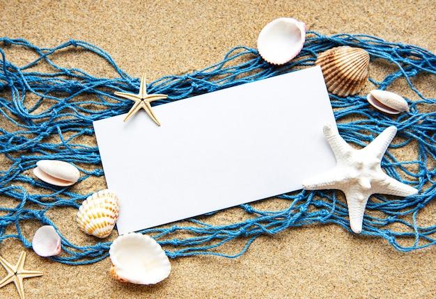 Cartão de papel em branco vazio na praia de areia com conchas do mar
