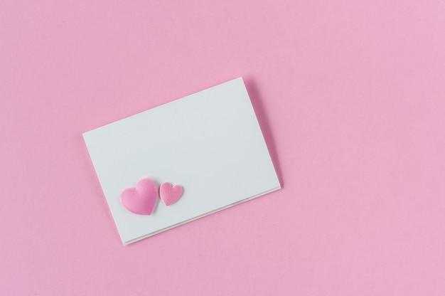 Cartão de papel em rosa com dois corações.